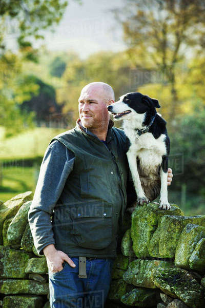 A sheep farmer, shepherd and his sheepdog standing beside him on a dry-stone wall. Royalty-free stock photo