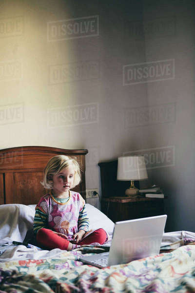 A three year old girl sitting on a bed in a hotel room, looking at a laptop computer screen intently,.  Royalty-free stock photo