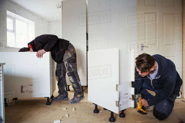 Two builders, building white kitchen units. Royalty-free stock photo