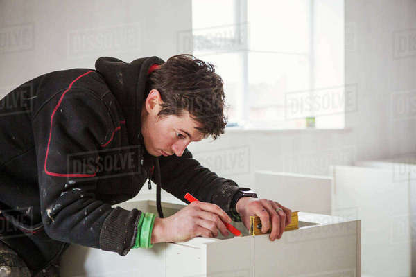 A builder, holding a pencil and ruler, measuring a kitchen unit. Royalty-free stock photo