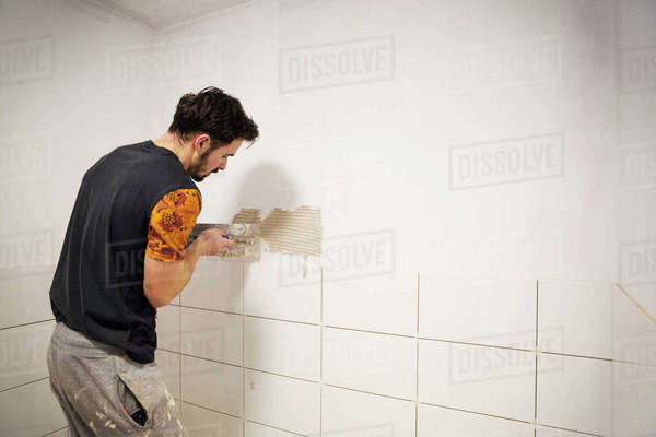 A builder, tiler placing white ceramic tiles on a wall in a bathroom. Royalty-free stock photo