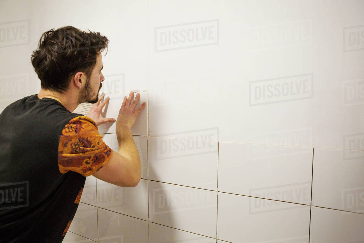 A builder, tiler placing white ceramic tiles on a wall in a bathroom ...