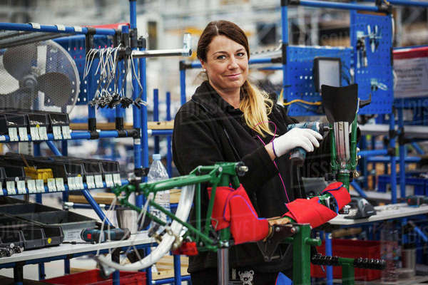 Female skilled factory worker assembling a bicycle in a factory working on the frame and wheels.  Royalty-free stock photo