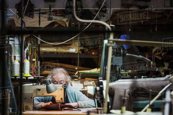 A senior grey haired woman worker sitting at a leather stitching machine in a shoemaker's workshop. Royalty-free stock photo