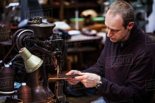 Man sitting at a large leather stitching machine in a shoemaker's workshop. Royalty-free stock photo