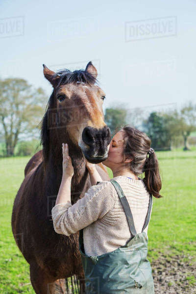 Woman standing outdoors, kissing a brown horse on the cheek. Royalty-free stock photo