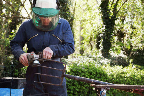 Man standing outdoors, wearing a face mask, working on a large metal garden fork or pitchfork with an angle grinder. Royalty-free stock photo