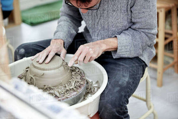 A man using a pottery wheel, shaping a pot base with a small handheld tool shaving off excess clay.   Royalty-free stock photo
