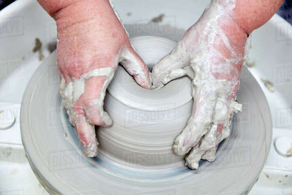 A person using a potter's wheel, throwing a clay pot and using thumbs to shape the wet clay. Seen from above. Royalty-free stock photo