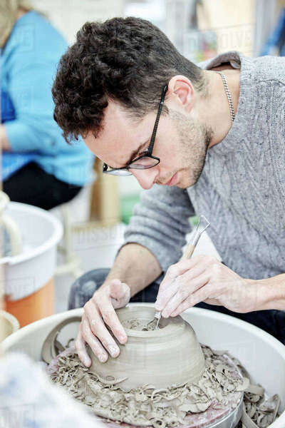 A man seated at a potter's wheel working and shaping a clay pot by removing excess clay.  Royalty-free stock photo