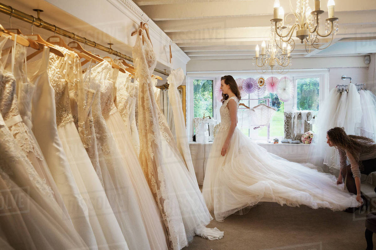 Rows Of Wedding Dresses On Display In A Specialist Dress Young Woman Trying With Long Train
