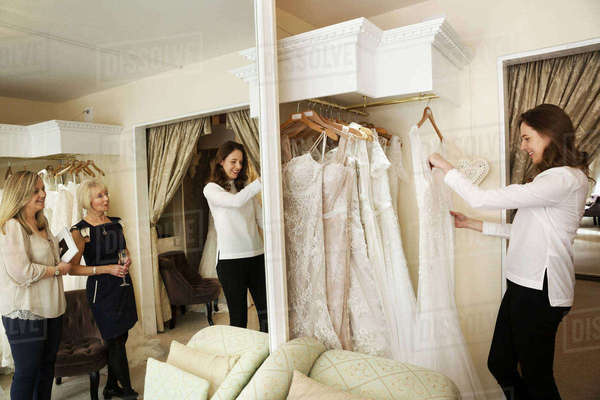Three women, a client and two retail advisors in a wedding dress shop, looking through the choice of gowns. Large mirror and rows of bridal gowns.  Royalty-free stock photo
