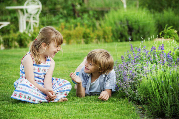A girl sitting on the grass talking to her brother lying beside her on a lawn in a garden. Royalty-free stock photo