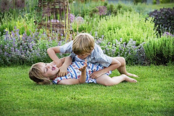 Smiling boy and girl in a garden, roughhousing, playing together, playfighting on a lawn. Royalty-free stock photo
