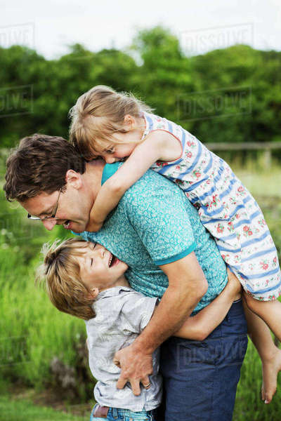 A father and two children in a garden, a boy hugging him around the waist and a girl on his back with arms around his neck.  Royalty-free stock photo