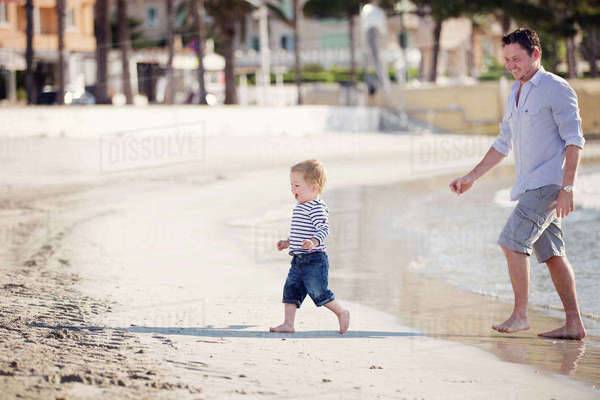 Smiling man and young boy wearing shorts walking on a sandy beach. Royalty-free stock photo