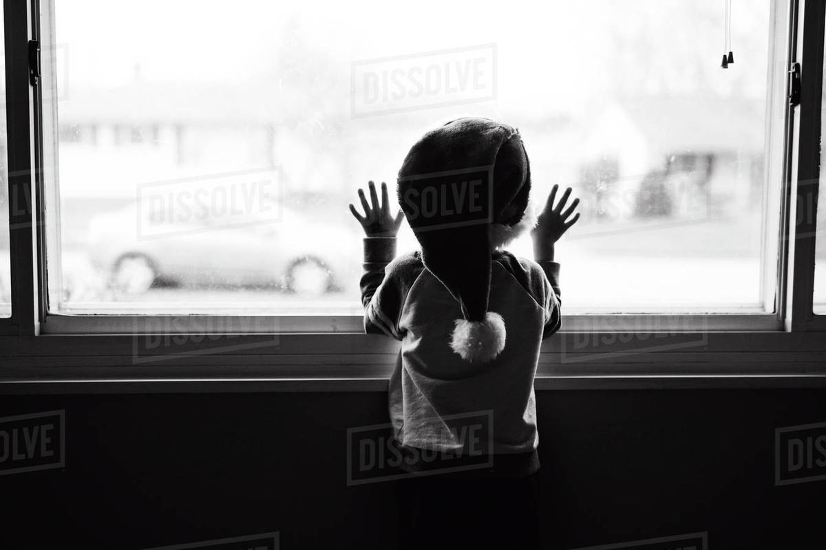 Boy Child Standing Looking Out Of A Window Wearing Santa Hat Stock Photo Dissolve