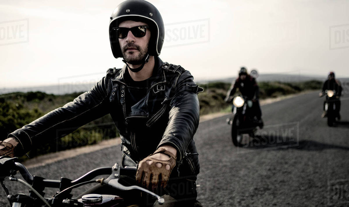 Man wearing open face crash helmet and sunglasses riding ...