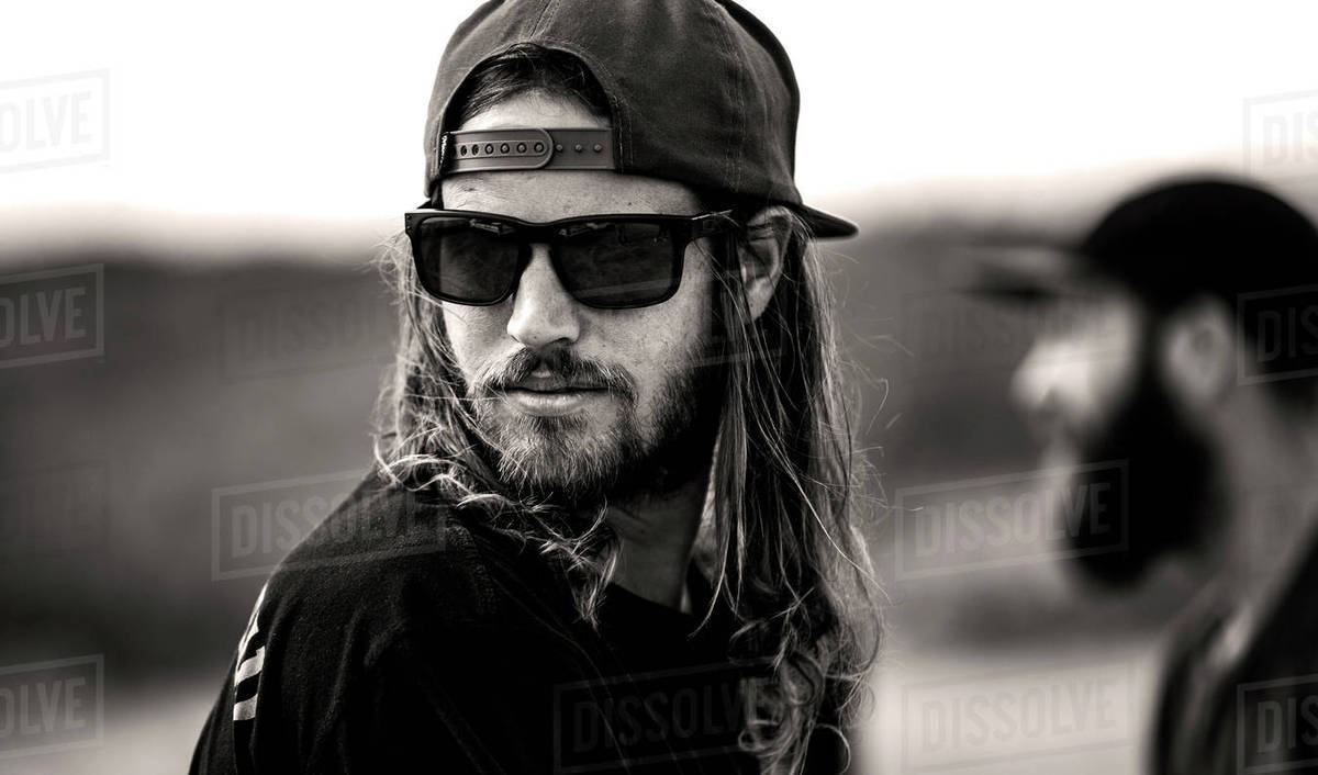portrait of bearded man with long hair wearing sunglasses and