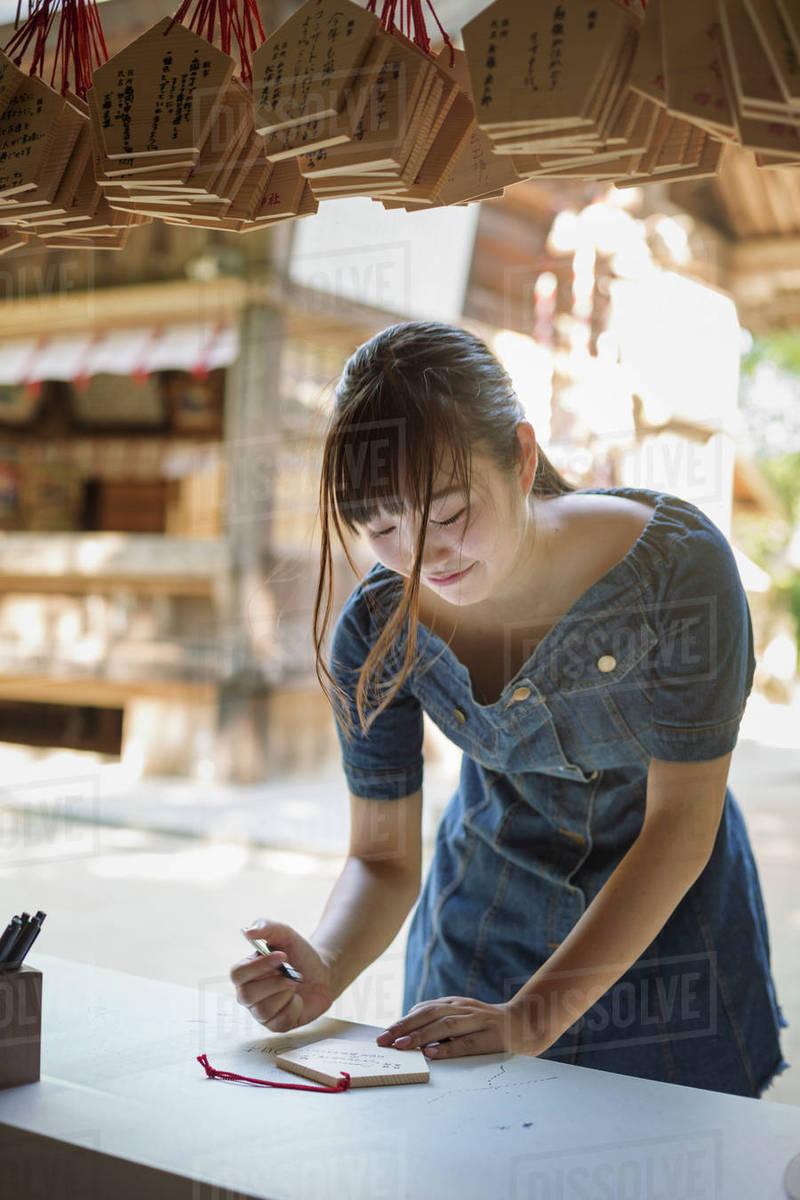 Young woman wearing blue dress writing on wooden fortune telling plaque at  Shinto Sakurai Shrine, Fukuoka, Japan  stock photo