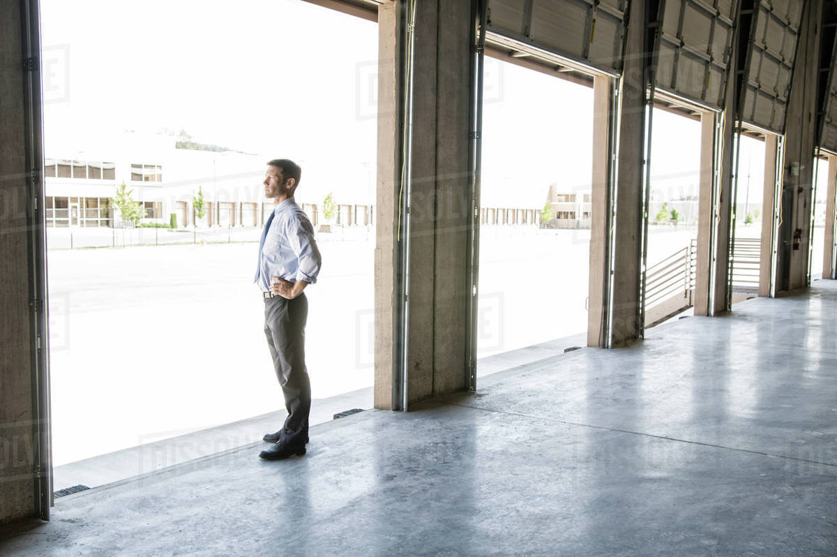 Caucasian Man In Shirt And Tie Standing In Loading Dock Door Of New Empty  Warehouse Anticipating The Arrival Of The First Truck Load New Business.