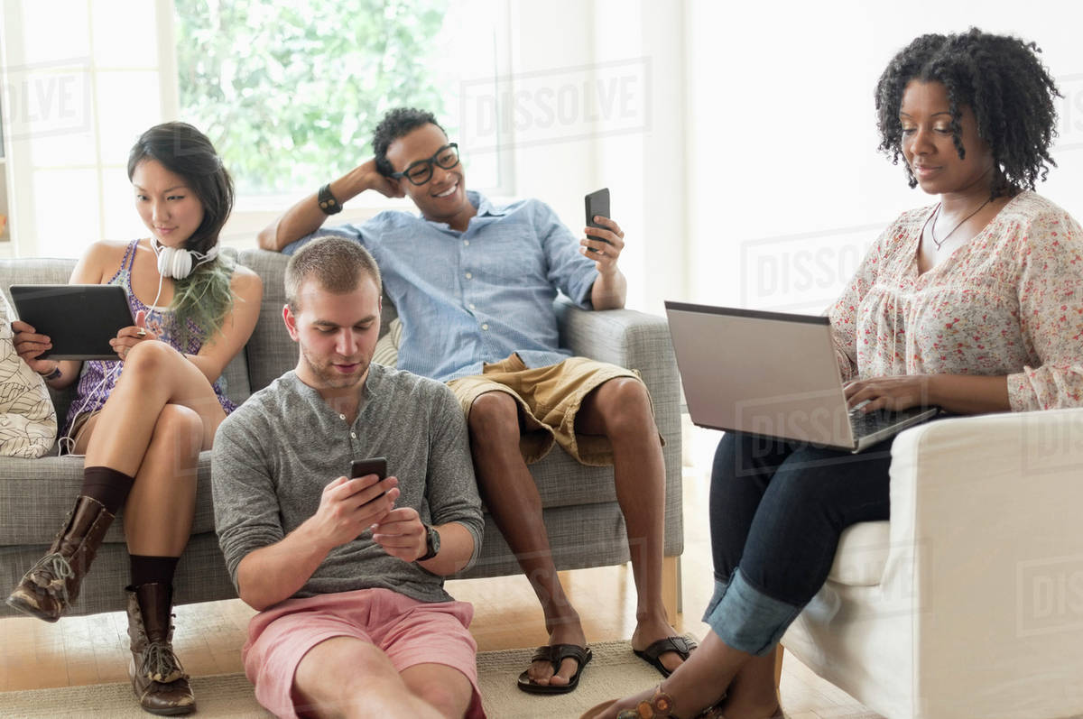 Friends hanging out in living room stock photo dissolve for Hanging groups of pictures