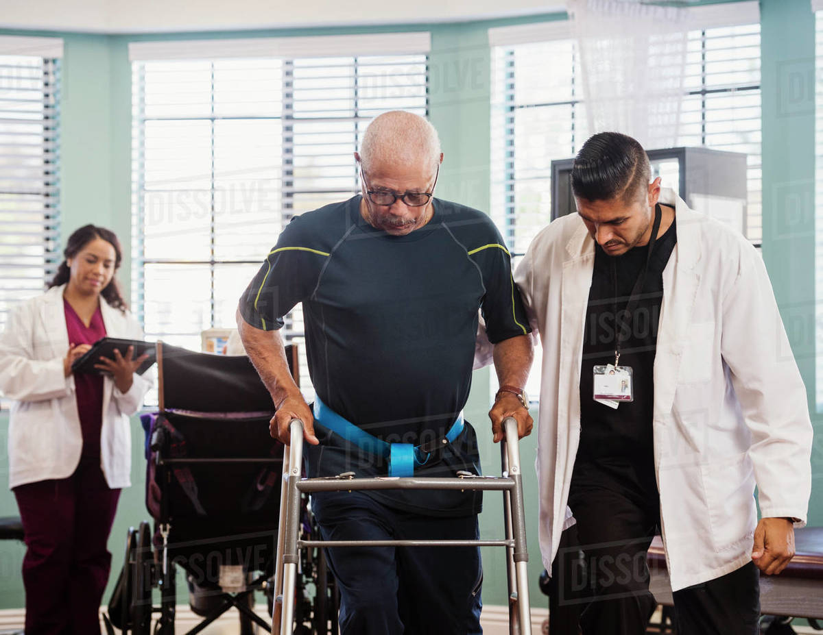 Senior man exercising with therapists during physical therapy Royalty-free stock photo