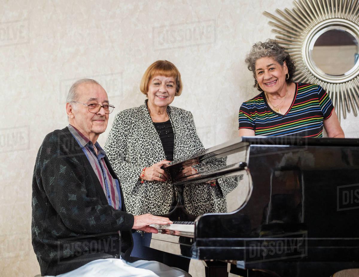 Senior women listening to man playing piano Royalty-free stock photo