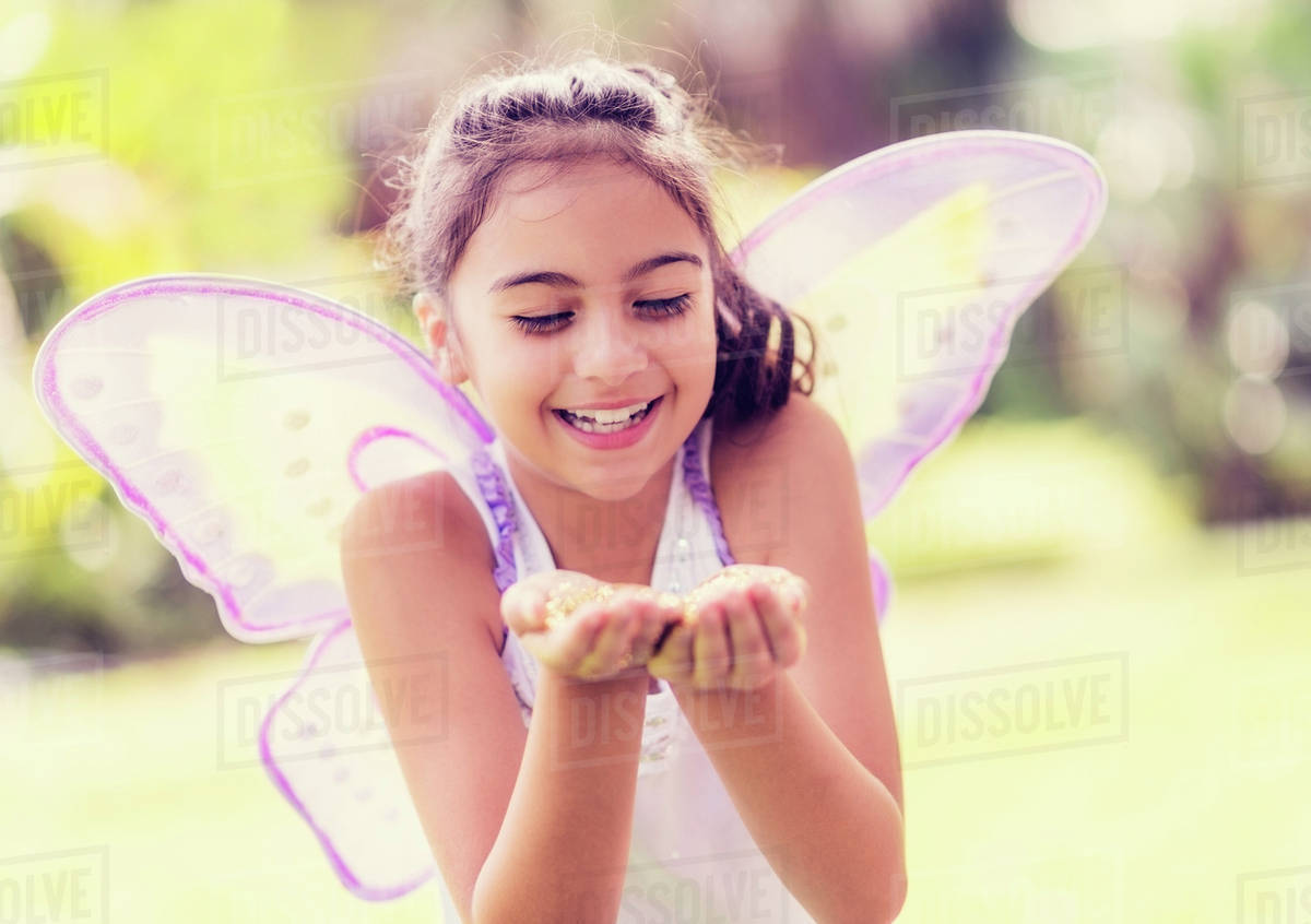 Girl (8-9) holding fairy dust in hands Royalty-free stock photo