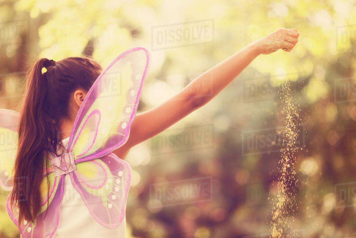 Girl (8-9) spreading fairy dust Royalty-free stock photo