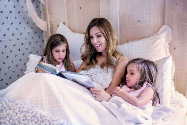 Mother reading bedtime story to her twin daughters (4-5) Royalty-free stock photo