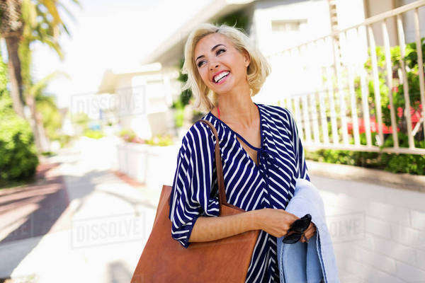 Woman wearing striped blouse walking street and smiling Royalty-free stock photo
