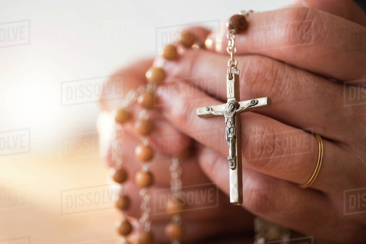 Woman Praying With Rosary Beads In Hands Stock Photo