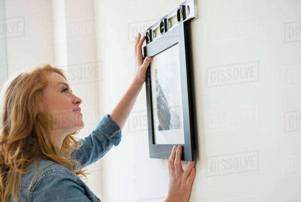 Woman hanging picture on wall Royalty-free stock photo