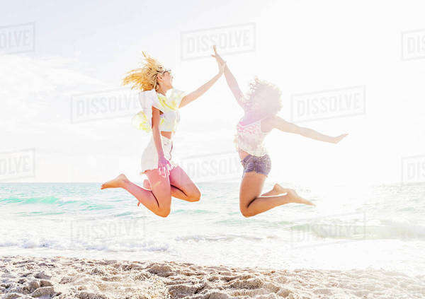Female friends jumping on beach Royalty-free stock photo