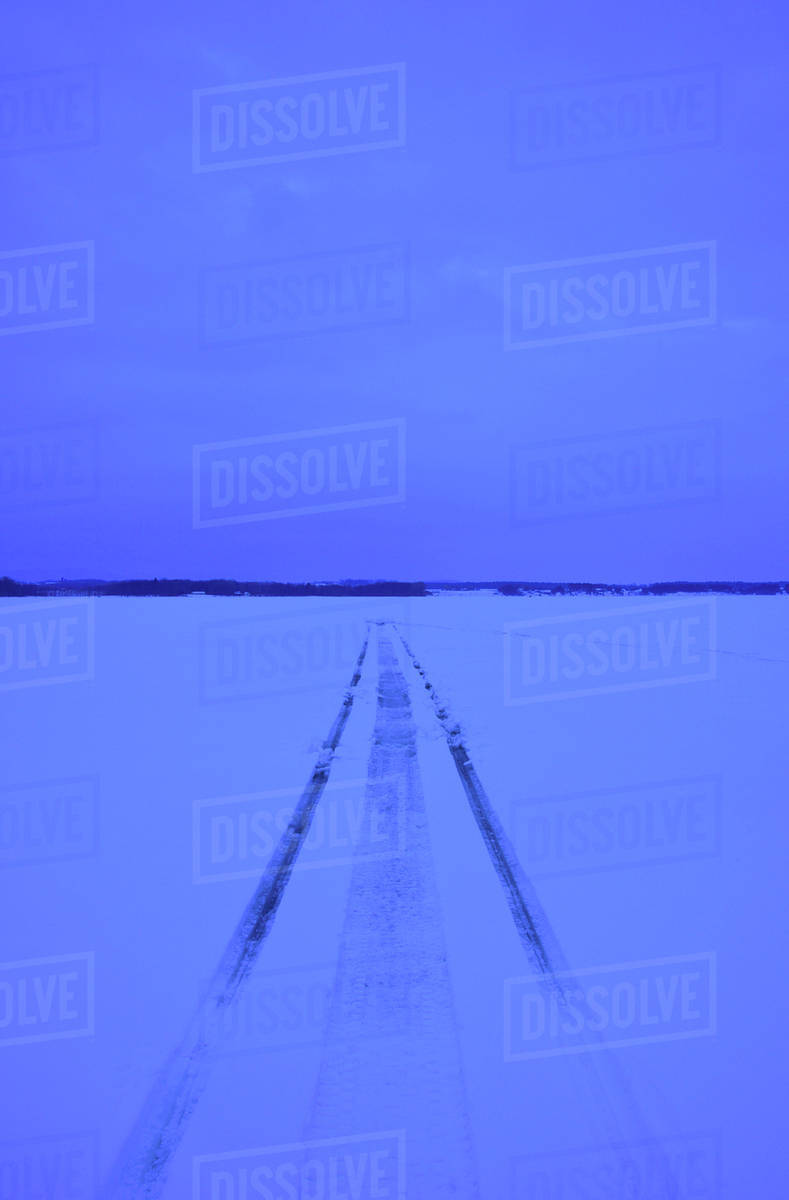 Snowmobile tracks on frozen lake stock photo