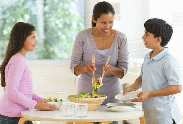 Mother with son (12-13) and daughter (10-11) preparing salad Royalty-free stock photo
