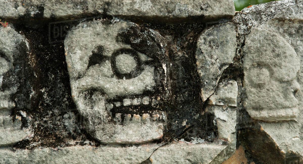Mayan carvings representing human skulls stock photo