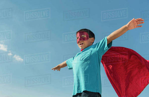 Boy (6-7) in superhero costume under blue sky Royalty-free stock photo