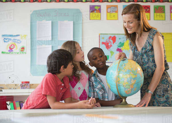Children (8-9) with female teacher learning in classroom Royalty-free stock photo