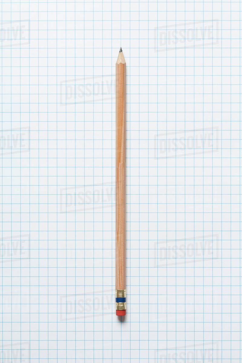 single wooden sharpened pencil on graph paper stock photo dissolve