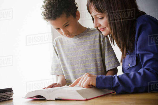 Schoolboy reading with teacher in classroom Royalty-free stock photo
