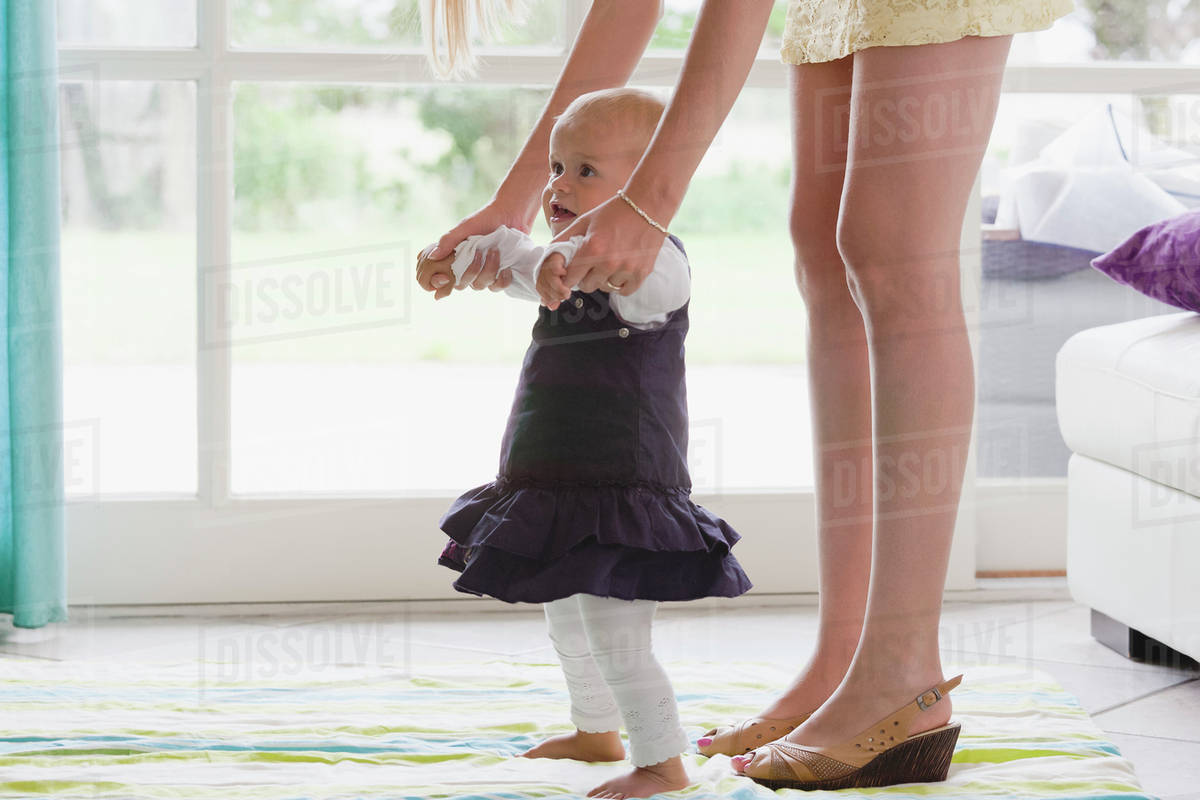 92468687163 Young mother supporting daughter with her first steps - Stock Photo ...