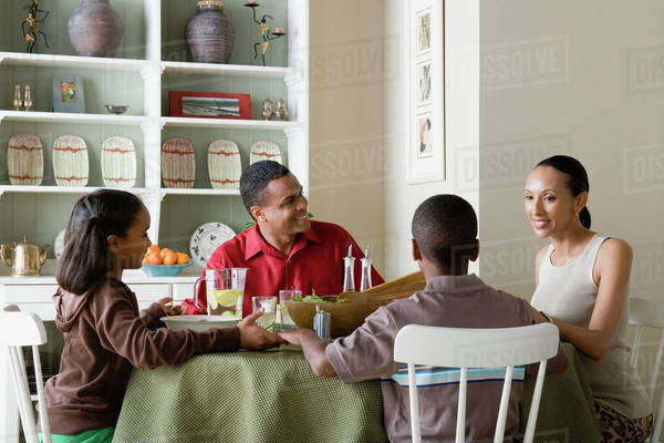 Parents and children (10-13) eating dinner together Royalty-free stock photo