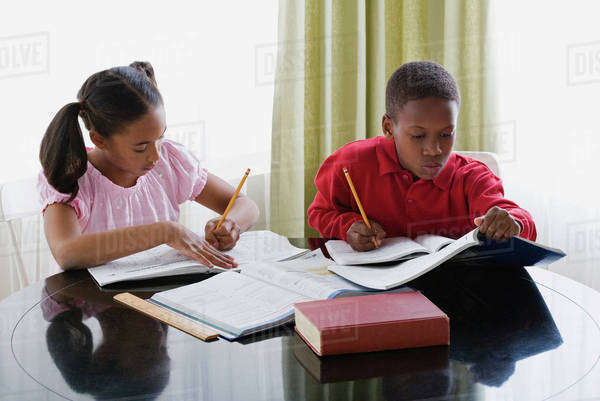 Brother and sister (10-13) doing homework Royalty-free stock photo