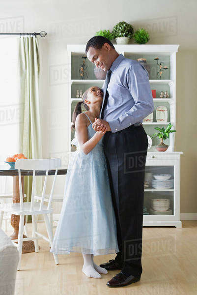 Father and Daughter (10-11) dancing in kitchen Royalty-free stock photo