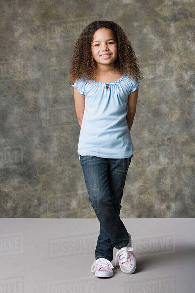 Portrait of smiling girl (8-9) standing, studio shot Royalty-free stock photo