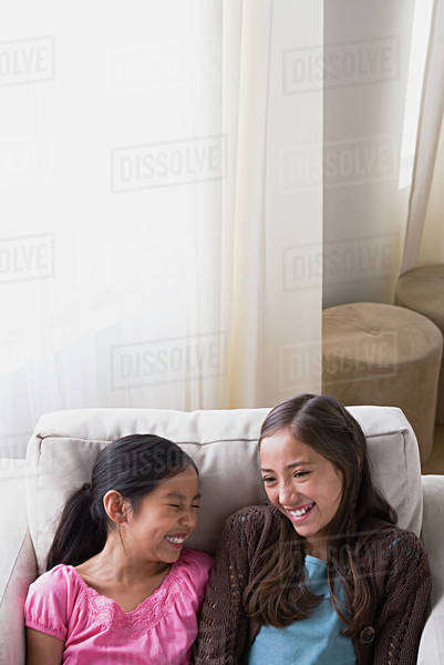 Sisters (8-9, 10-11) laughing in armchair Royalty-free stock photo