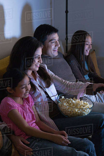 Family with two daughters (8-9, 10-11) watching tv on sofa Royalty-free stock photo