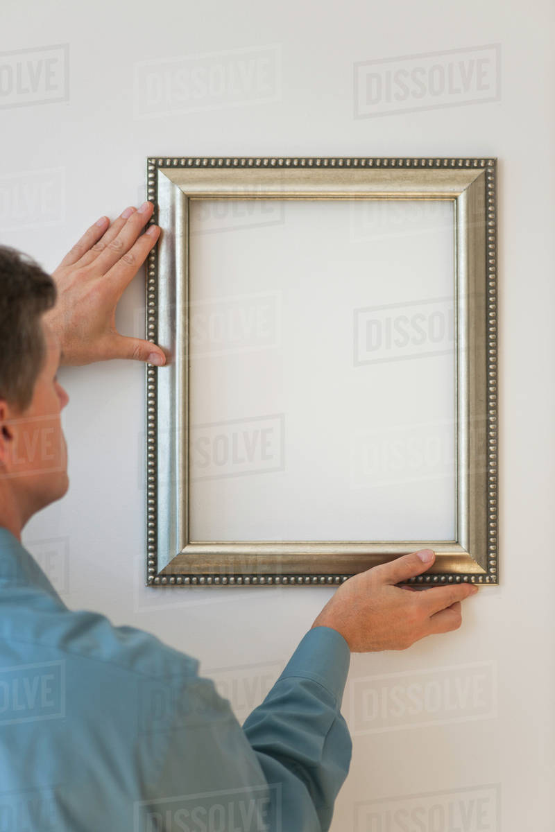 Man hanging silver frame on wall - Stock Photo - Dissolve